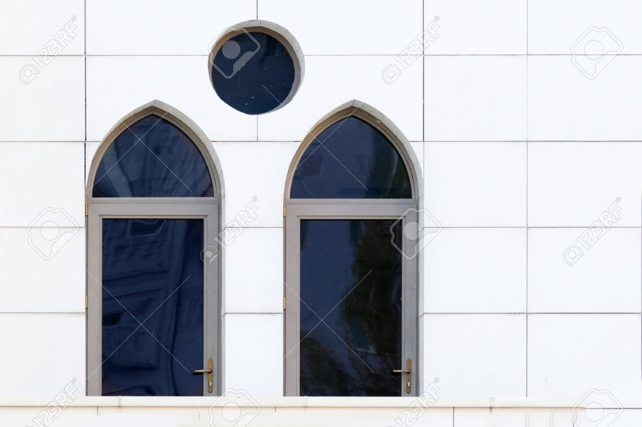 107657394 white wall with an arched and round windows detail of building exterior urban geometry copy space ab
