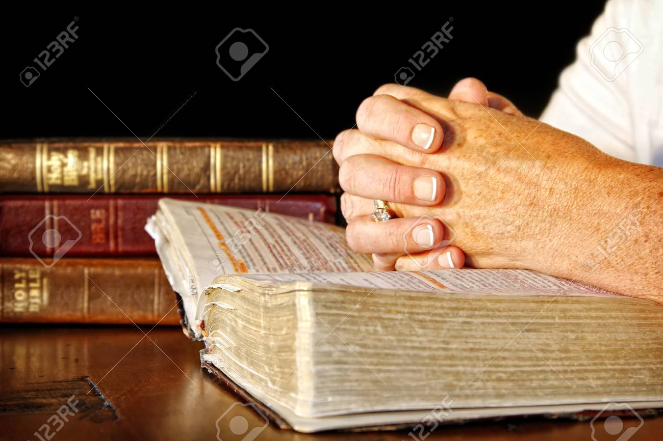 A woman clasps her hands in prayer on an open Holy Bible, while
