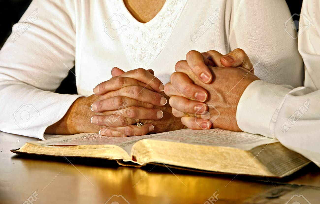 A married couple wearing white shirts clasp their hands in prayer