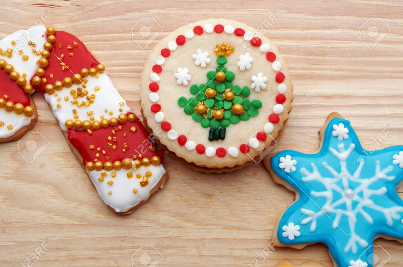 Artistically Decorated Christmas Cut Out Cookies On Wood Grain