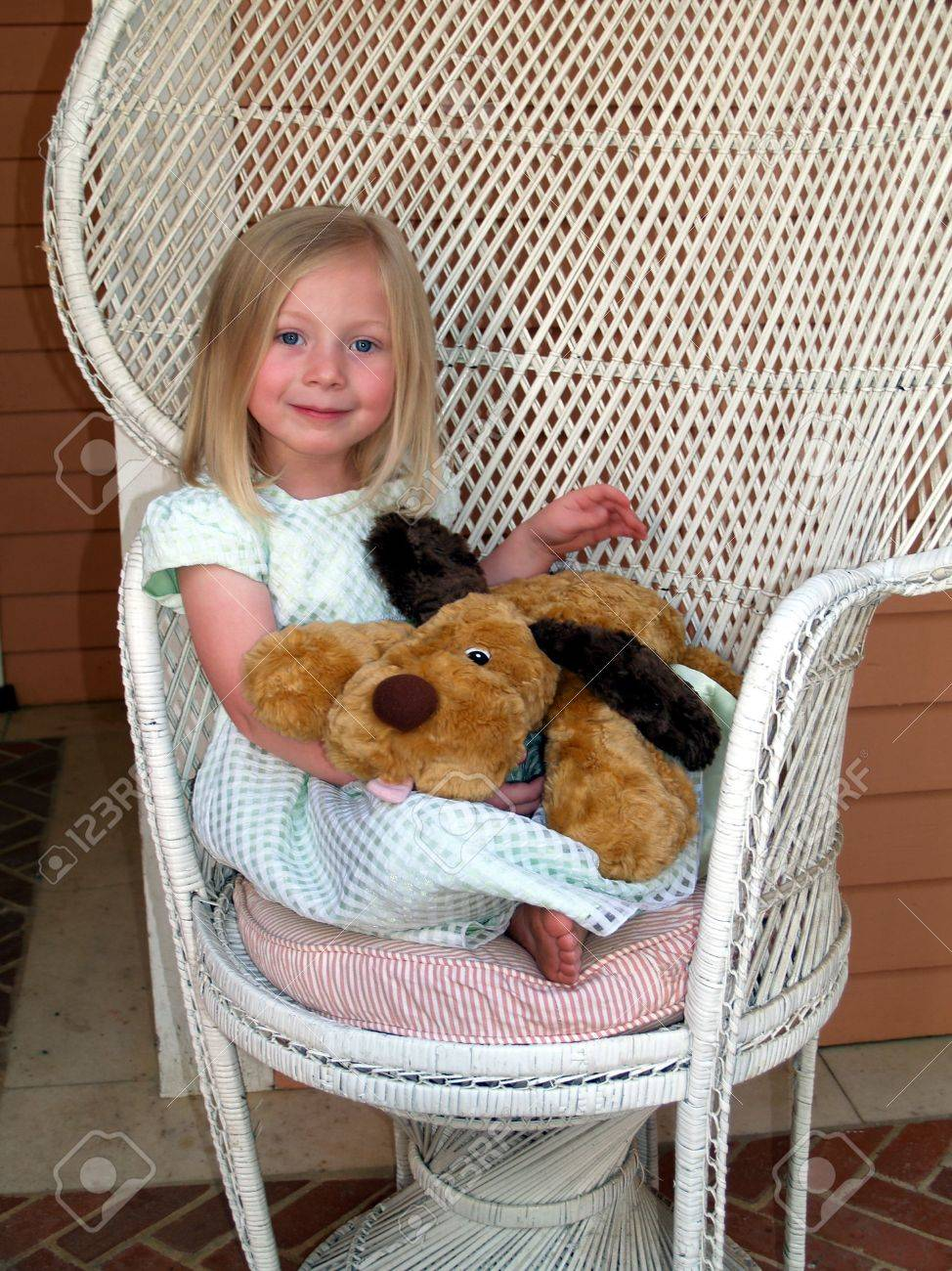 Young Girl With Stuffed Puppy In Her Lap Sitting In A Rattan Stock