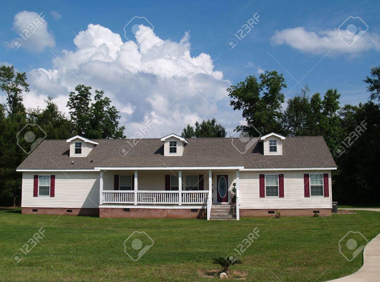 One story residential home with vinyl siding on the facade and a brick foundation. Stock Photo - 5168201