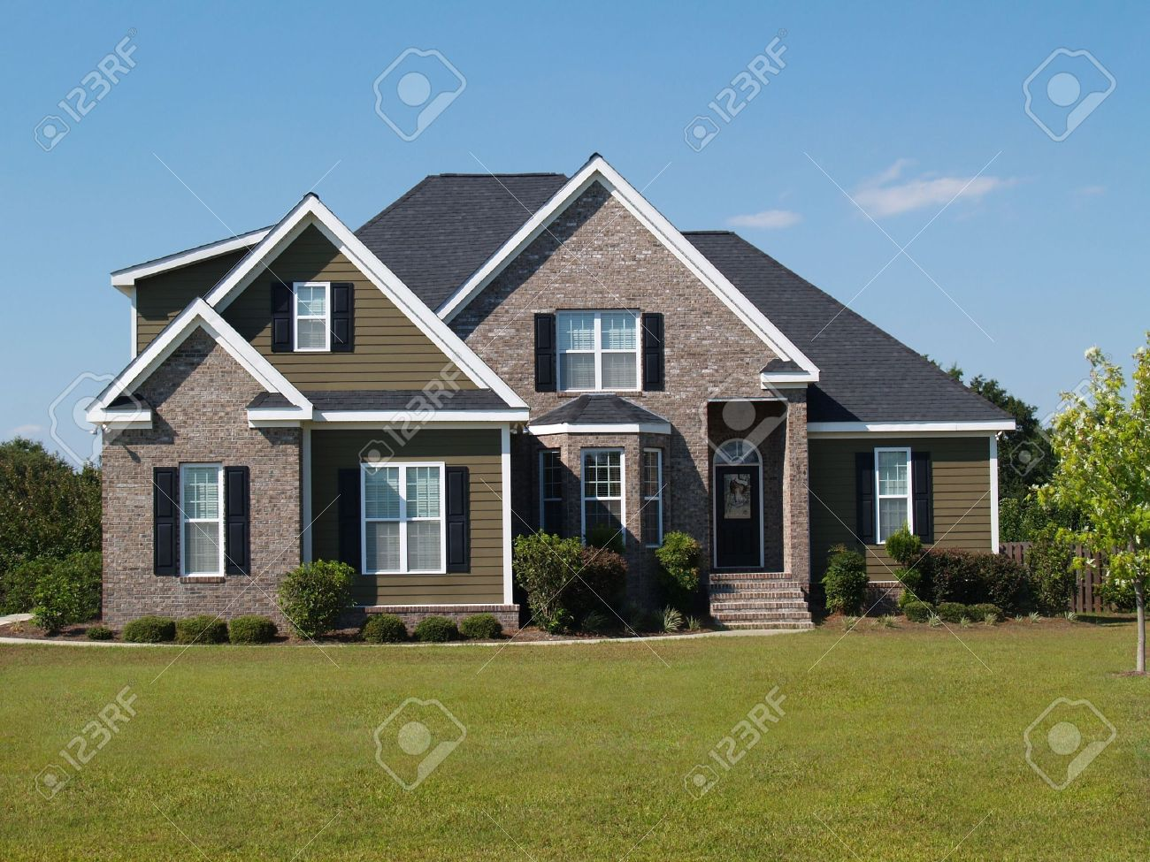 Two story brick and vinyl residential home with bay window. - 5580911