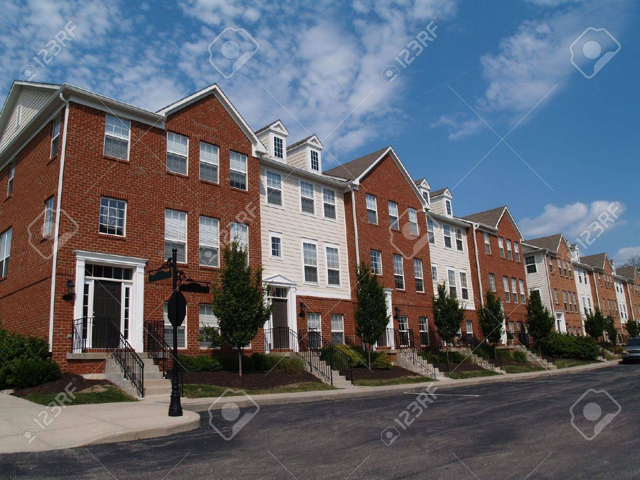 A row of brick condos or townhouses beside a street. - 5294815