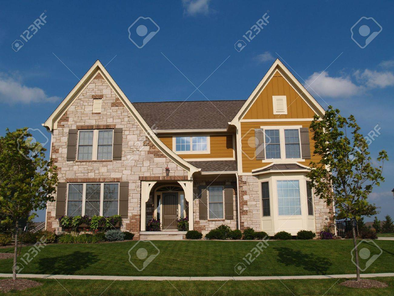Two story stone, brick and board sided residential home with bay window. - 5458651