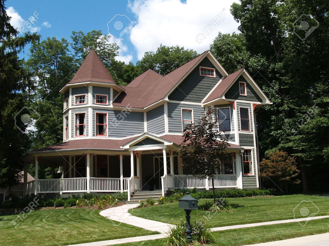 New two story Victorian residential home with vinyl or board siding on the facade styled after an old-fashioned historical house with bay windows, gingerbread and a turret. - 5520112