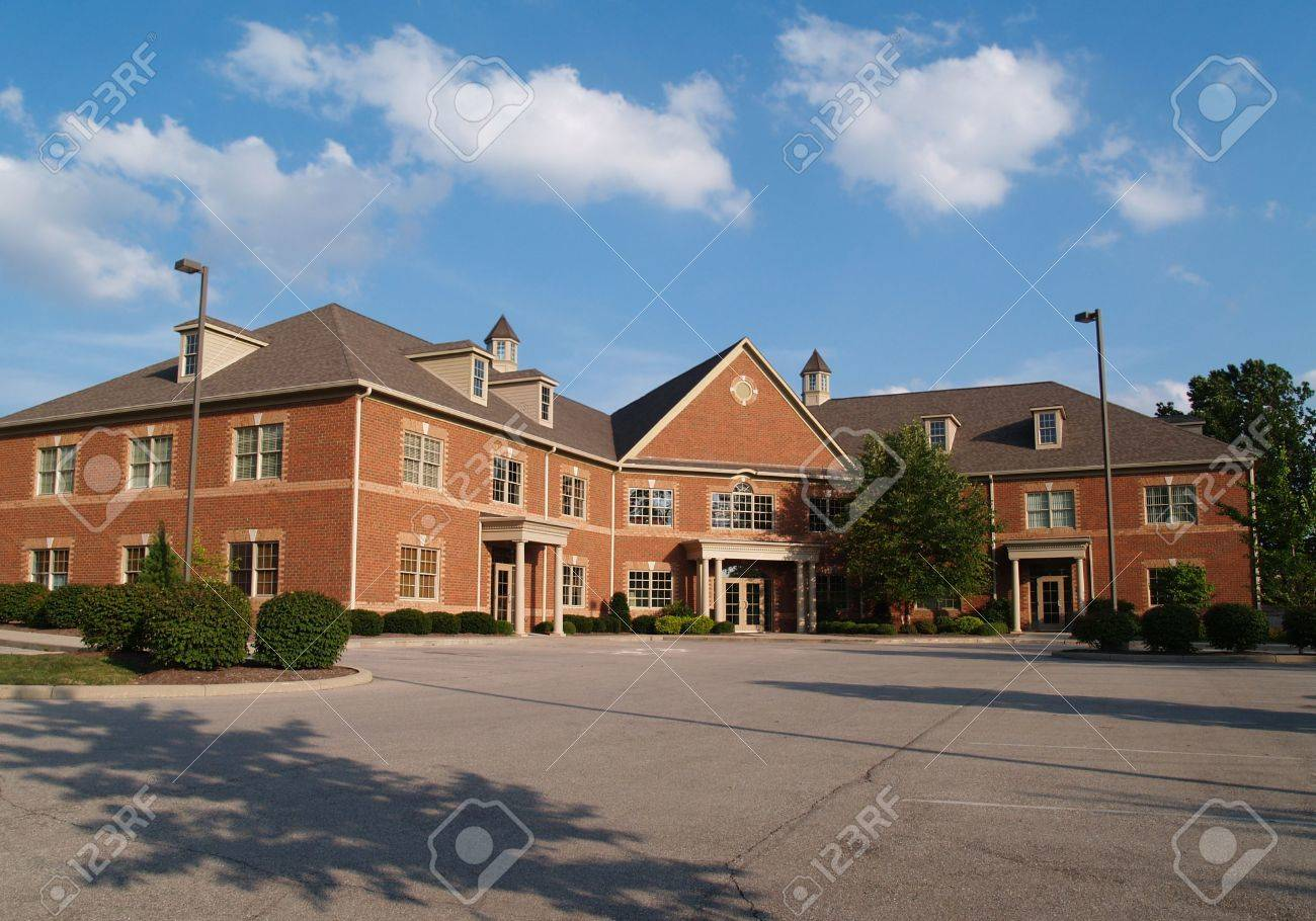 Two story red brick office building with parking spaces. - 5520097