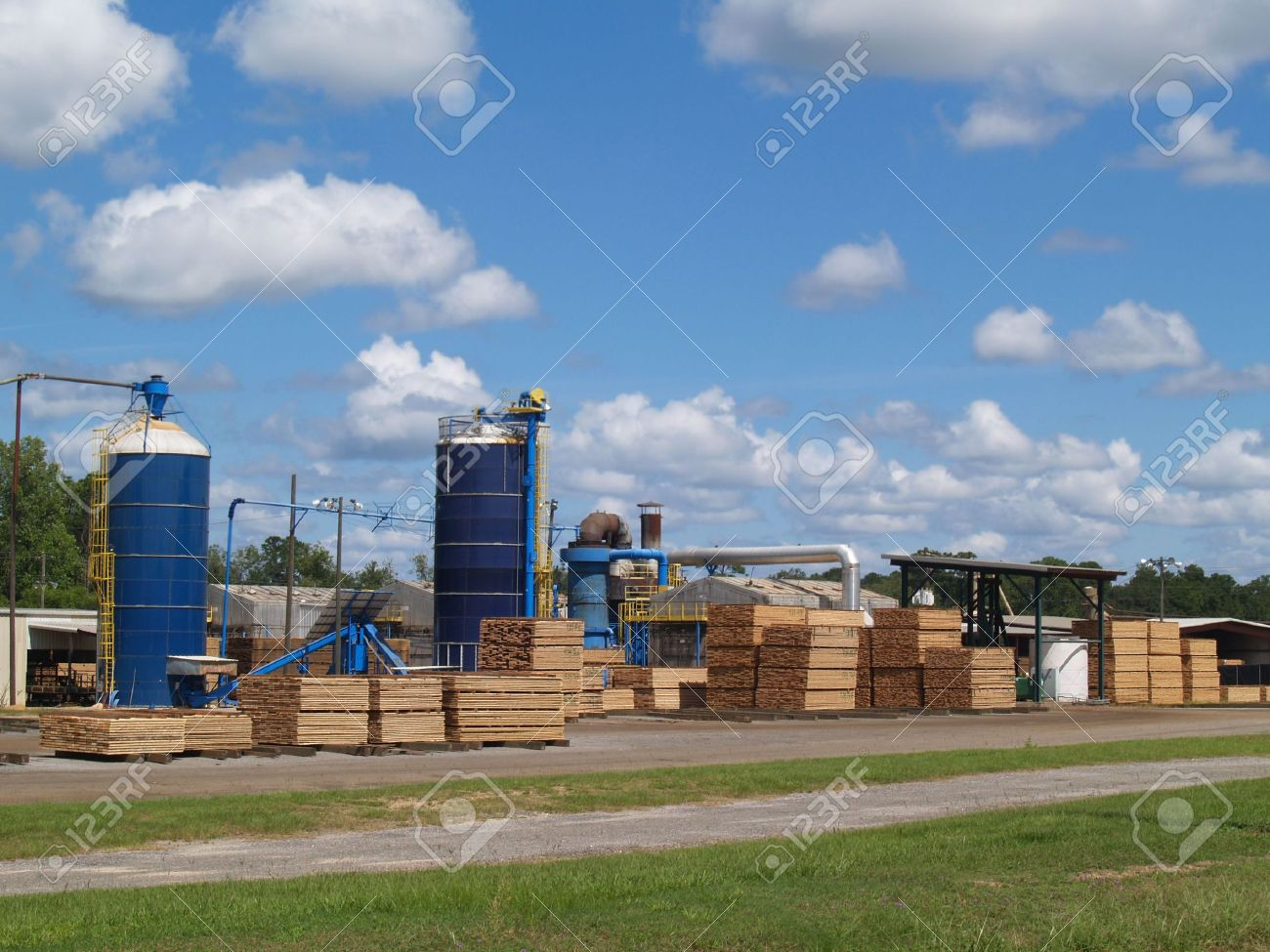 Outside view of a south Georgia lumber yard with blue silos and stacks of fresh cut green lumber curing in the sunshine. - 5608279