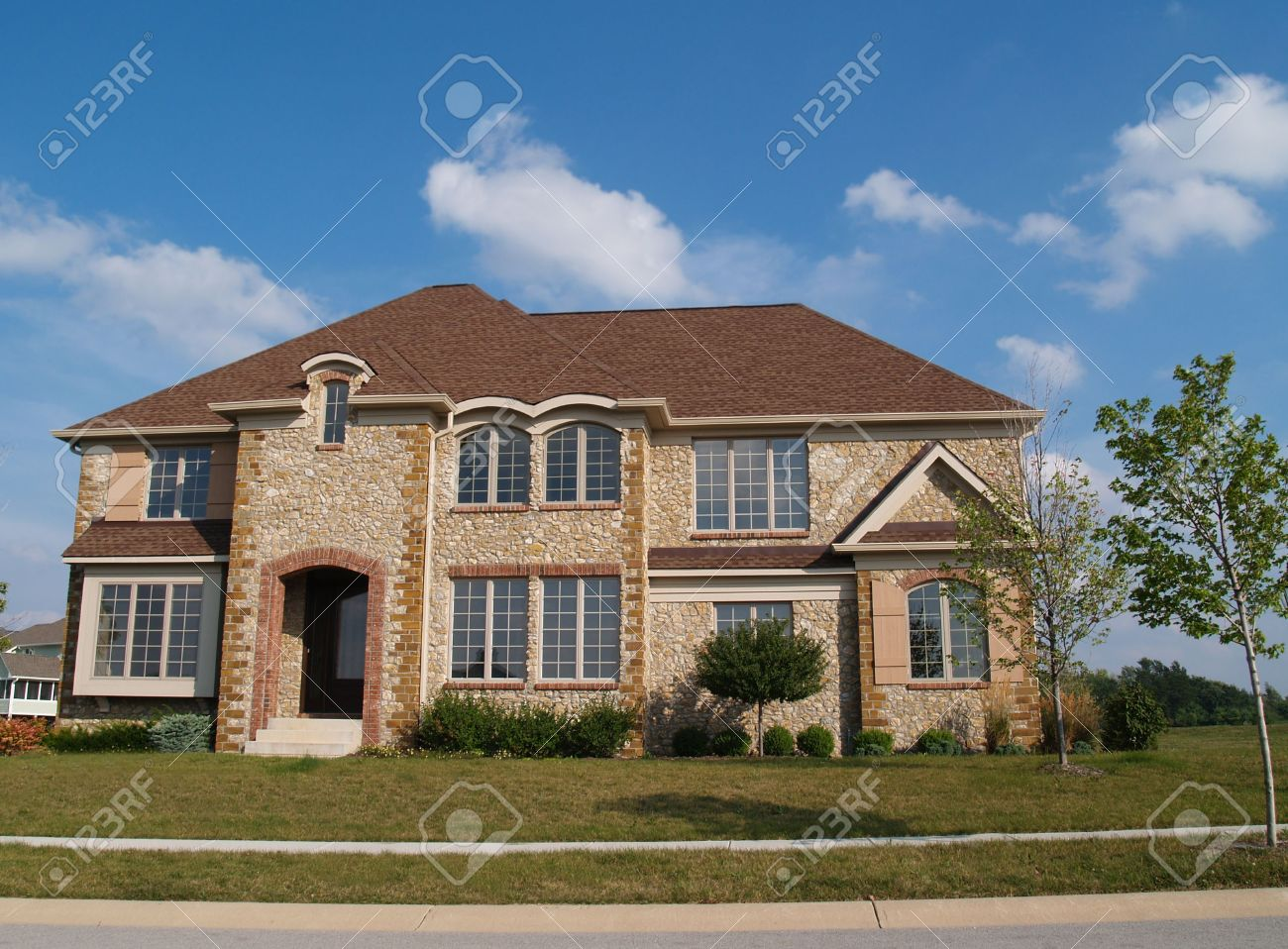 Two story contemporary stone residential home with arched windows. Stock Photo - 5862576