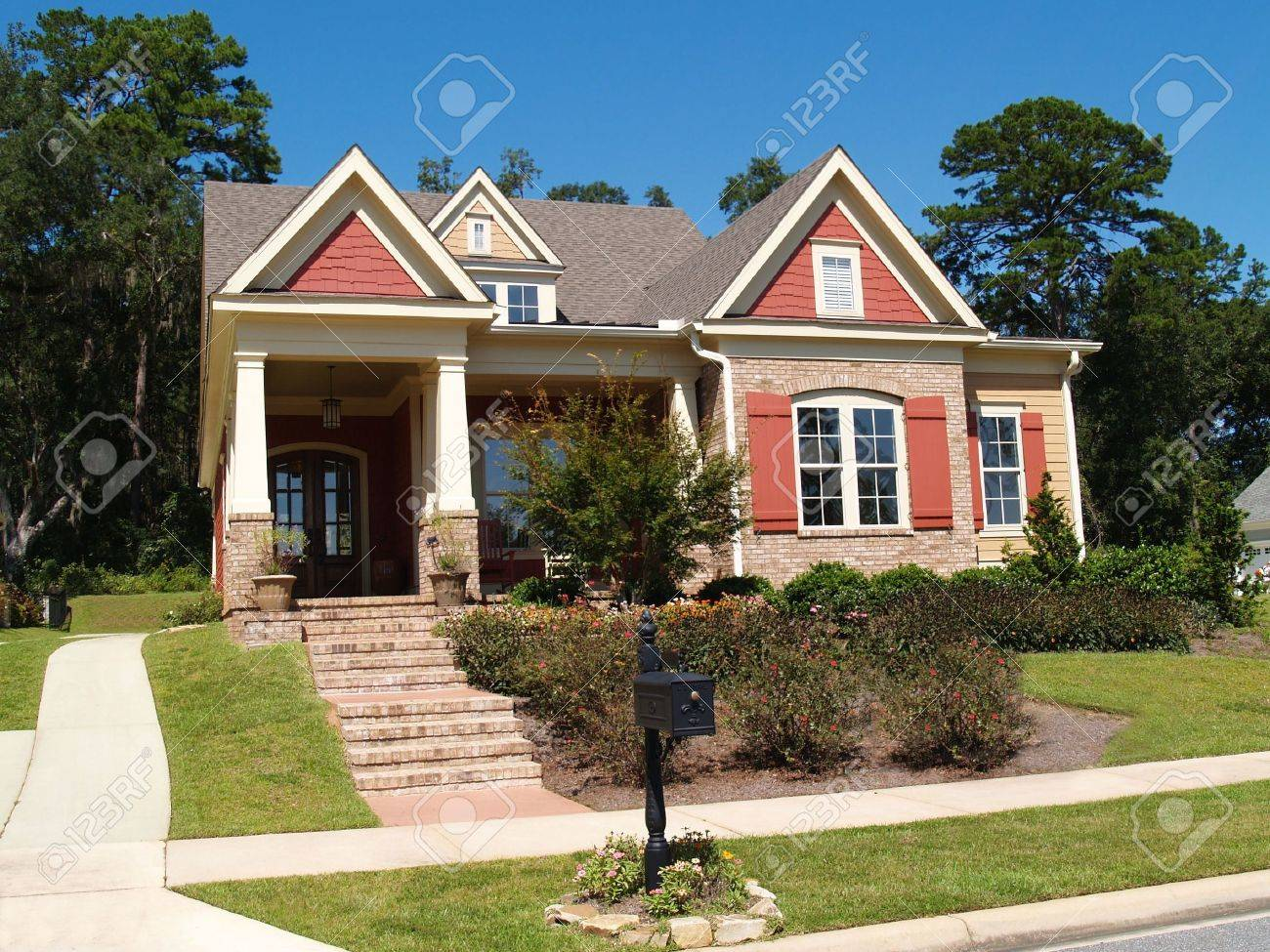 Beige brick home having peach and white trim with steps leading up to squares columns on the porch. - 6511098