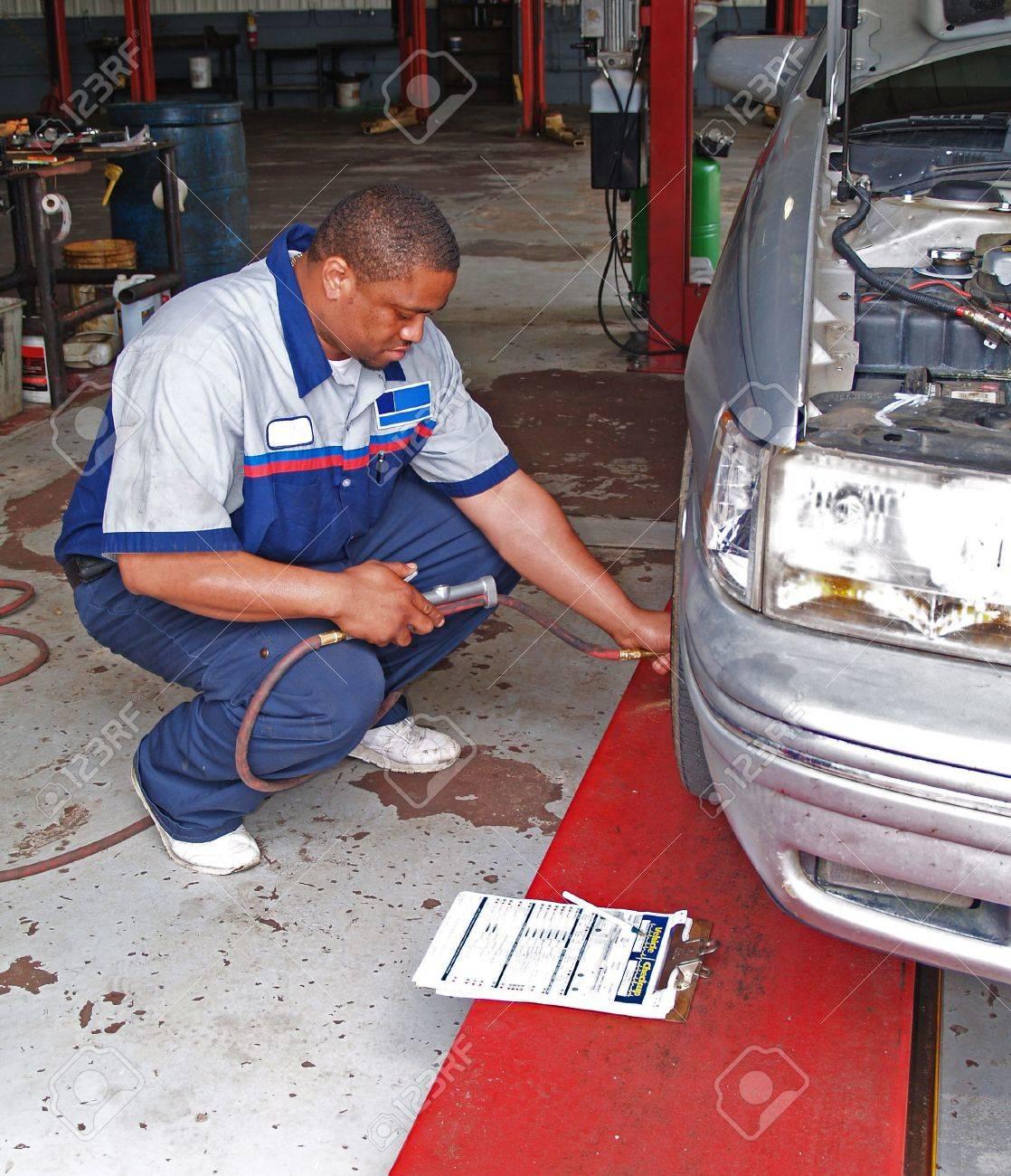Auto mechanic inspecting a car's tire pressure in a service garage. - 7442809