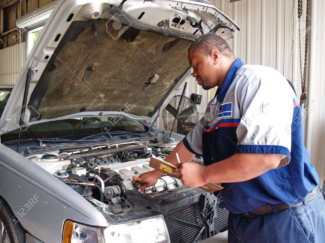 Mechanic Performing a Routine Service Inspection - 7765991