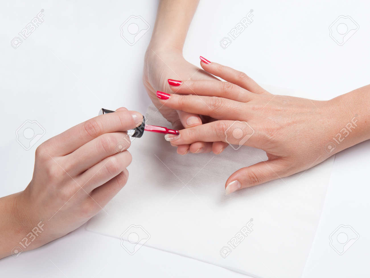 Closeup shot of woman`s hands in a nail salon receiving a manicure on a white background - 134286201