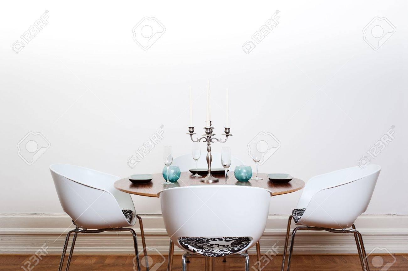 Modern Dining Room With A Round Table And White Chairs And Background.  Stock Photo