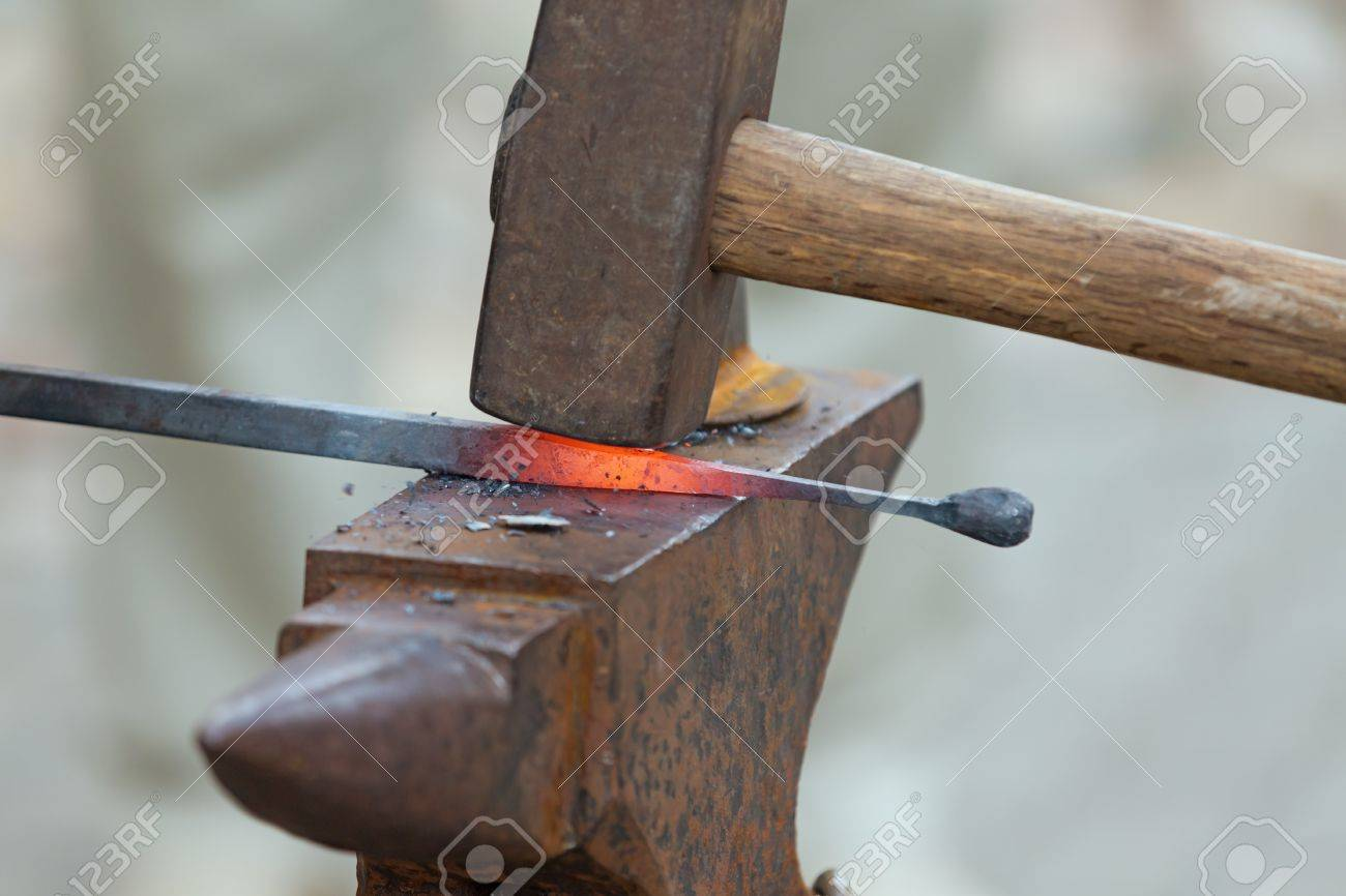 blacksmith anvil and hammer. blacksmith working metal the oldfashioned way, with hammer and anvil open fire stock photo
