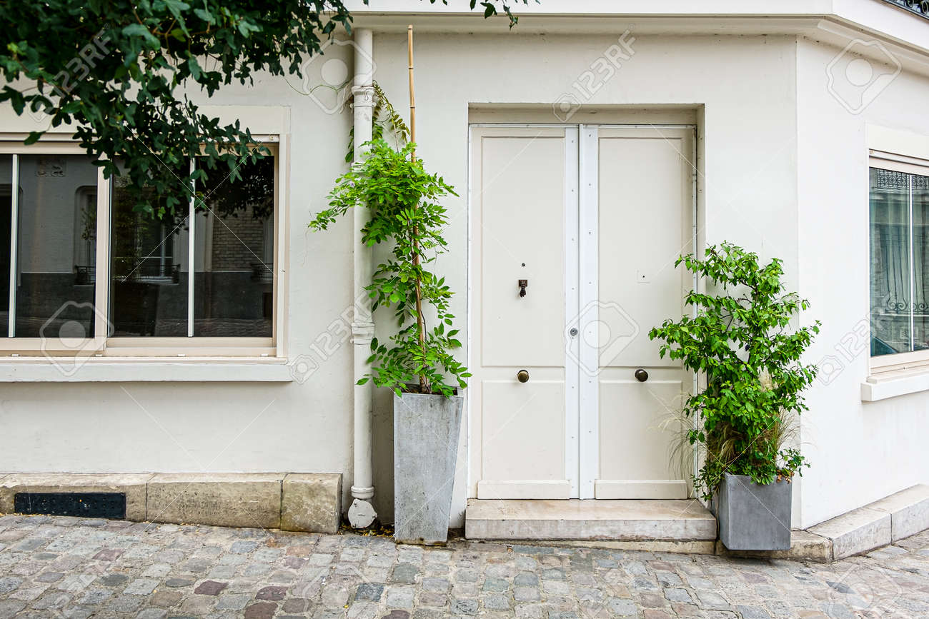 A milky white house on the corner in Montmartre, Paris, with potted plants placed on the stone road at the door - 171696173