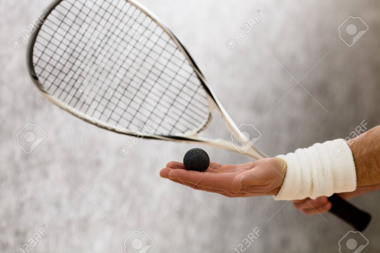 Closeup of squash racket and one ball in man's hand. Black-coloured ball represented on man's hand who is on court. - 57167569