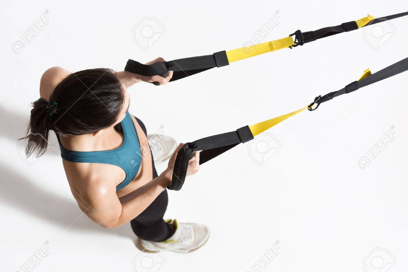 Top view of pretty young lady training upper body on suspension trainer sling. - 61960706