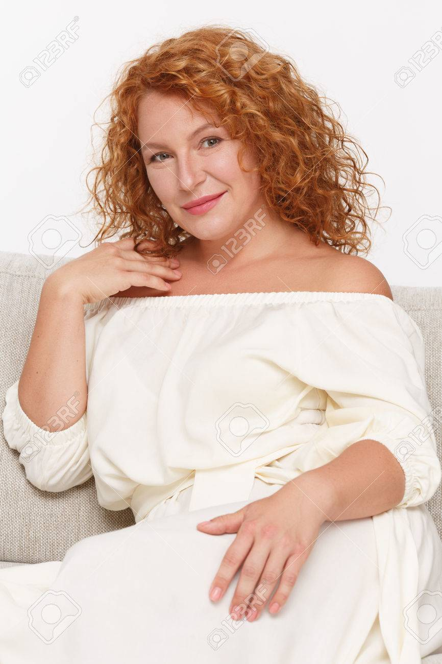portrait of seductive or temping mature or middle aged woman looking at camera and smiling isolated