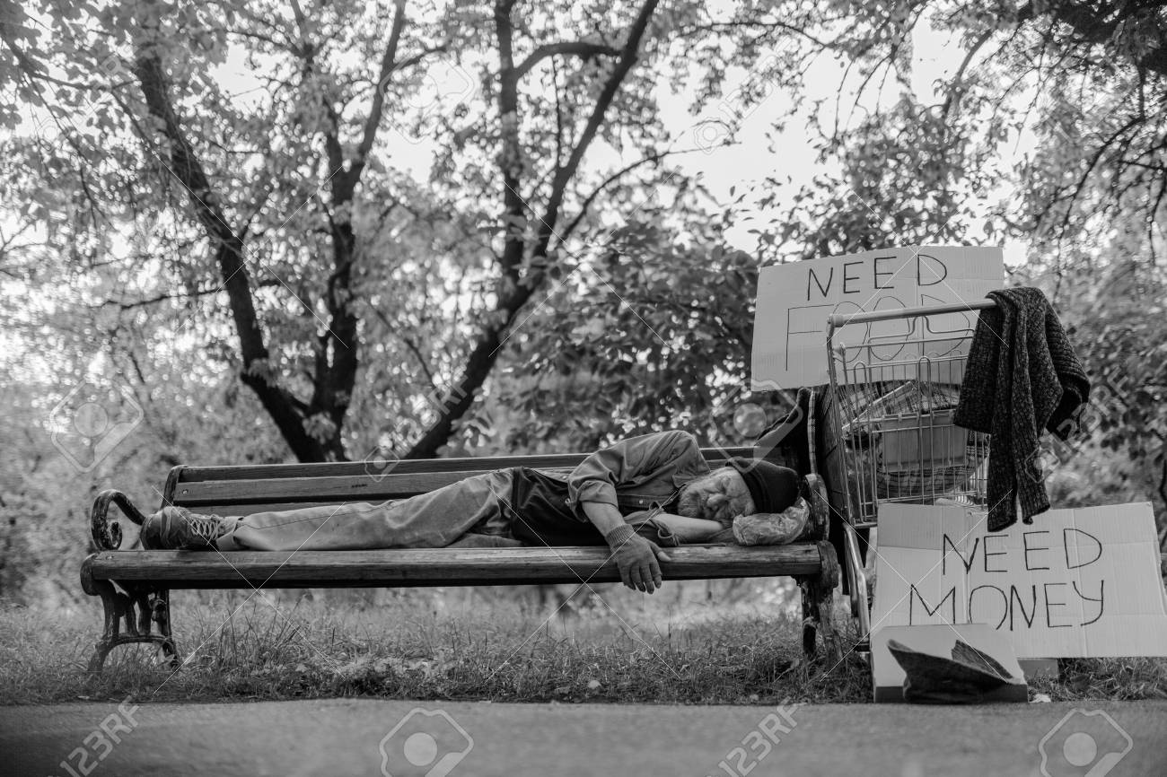 Black and white portrait of homeless man lying on bench