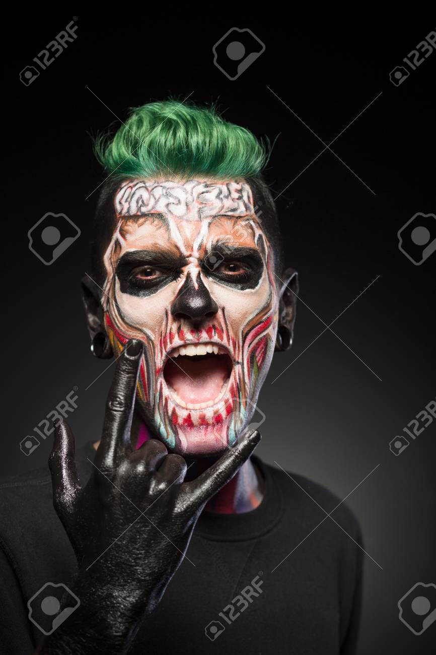 Man with halloween makeup showing tongue. Stylish zombie makeup..