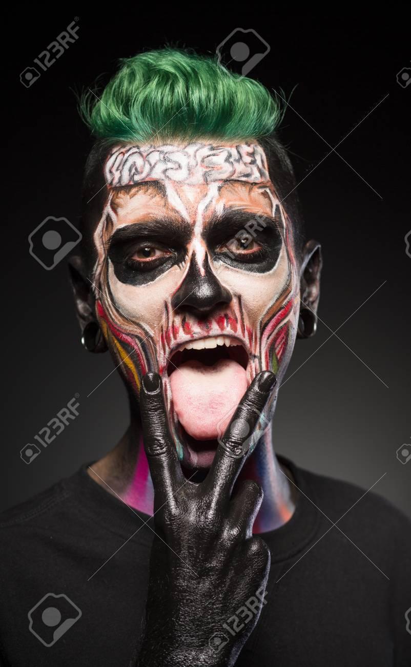 face art man with green hair and bright skull makeup showing tongue halloween makeup