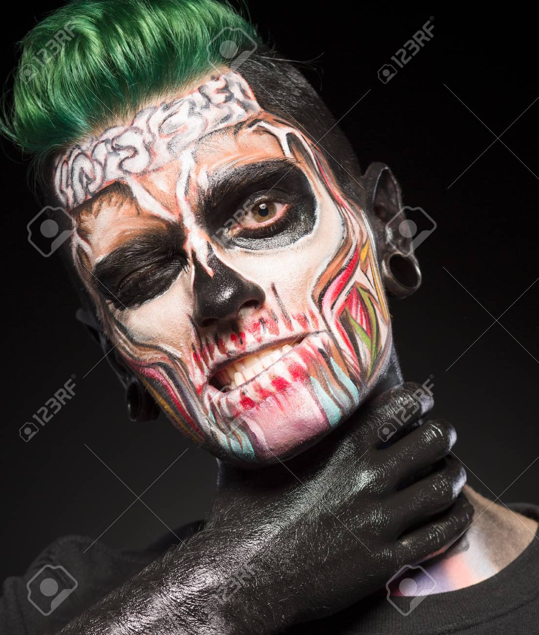 Scared Halloween makeup. Zombie monster touching neck with hand..