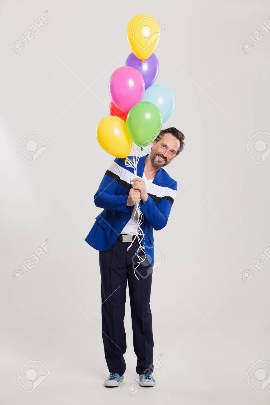 Handsome Man In Mixed Suit Holding Balloons Happy Birthday Concept Stock Photo