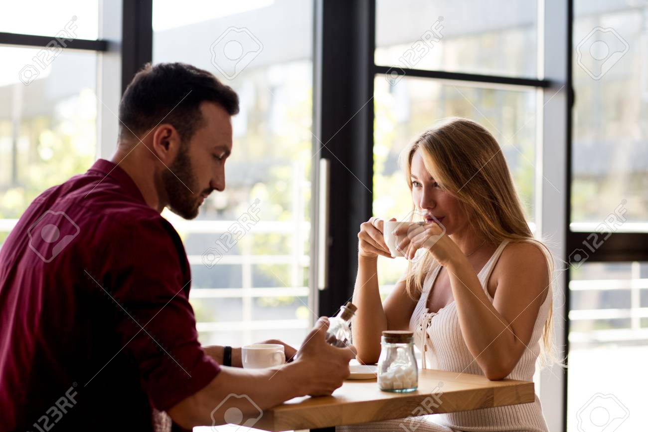 377d33c9219 Stock Photo - Young Couple In Fashion Clothes Having Tasty Coffee In Cozy  Cafe. Making Plans For Future. Love Story Concept.