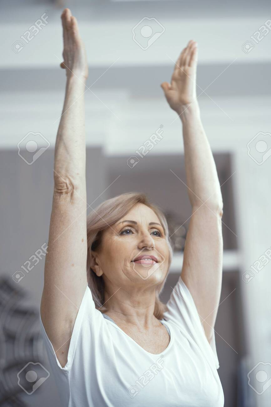 A Woman Over 50 Years Old Loves Yoga She Raised Her Hands In Stock Photo Picture And Royalty Free Image Image 119686261