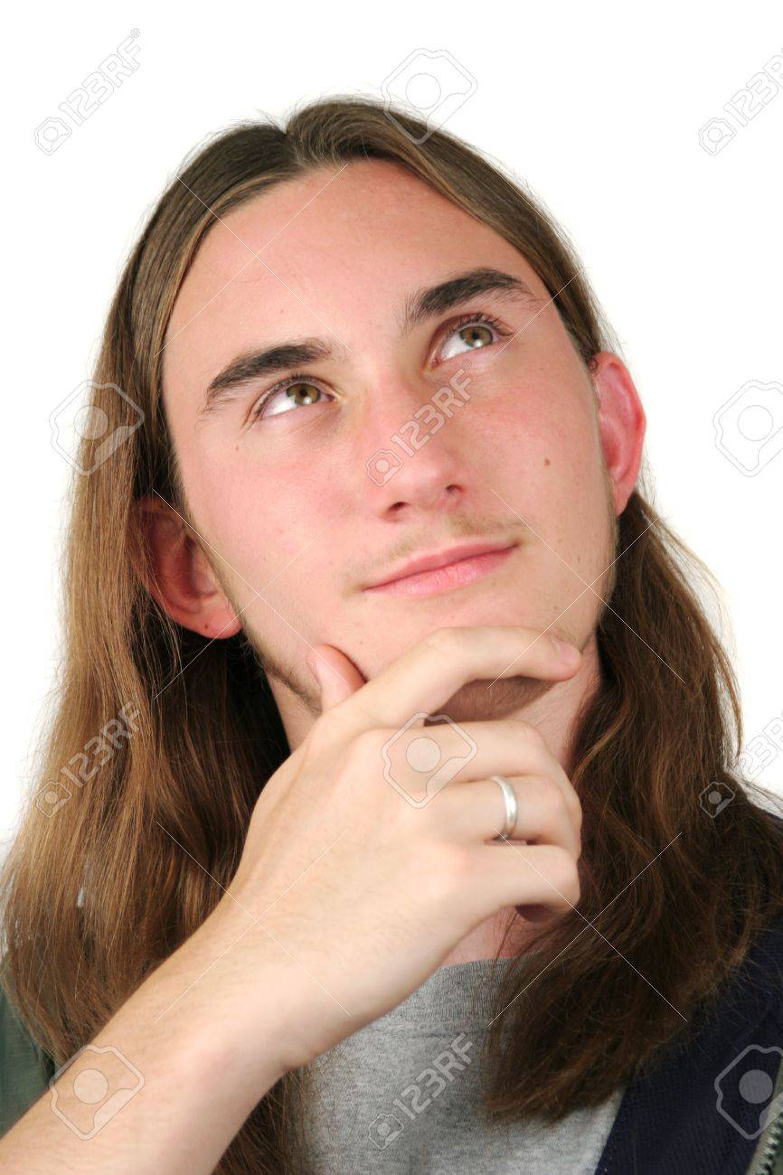A handsome teenaged boy with long hair, coming up with an idea.  Isolated. Stock Photo - 208533