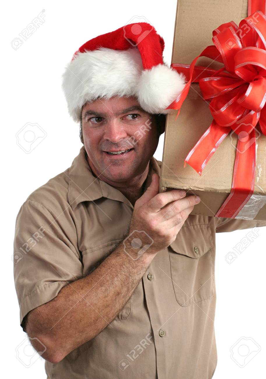 a delivery man in a Santa hat listening to a gift he's supposed to deliver Stock Photo - 233578
