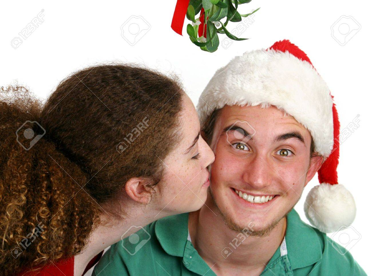 A teen girl kissing a very surprised boy under the mistletoe. Stock Photo - 277482
