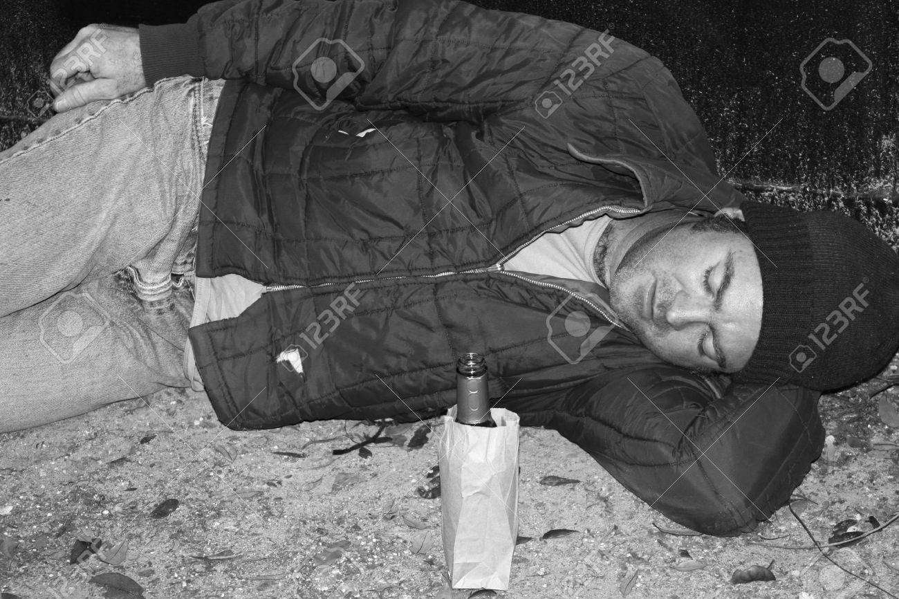 A black and white photo of a homeless man sleeping on the ground
