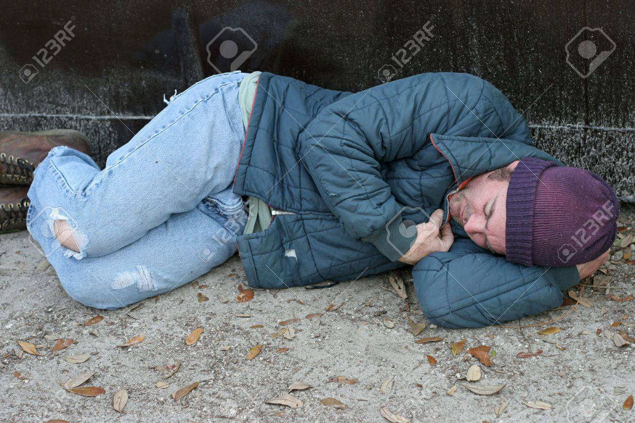 7ca12ff271 A homeless man sleeping on the ground beside a dumpster. Stock Photo -  1406744