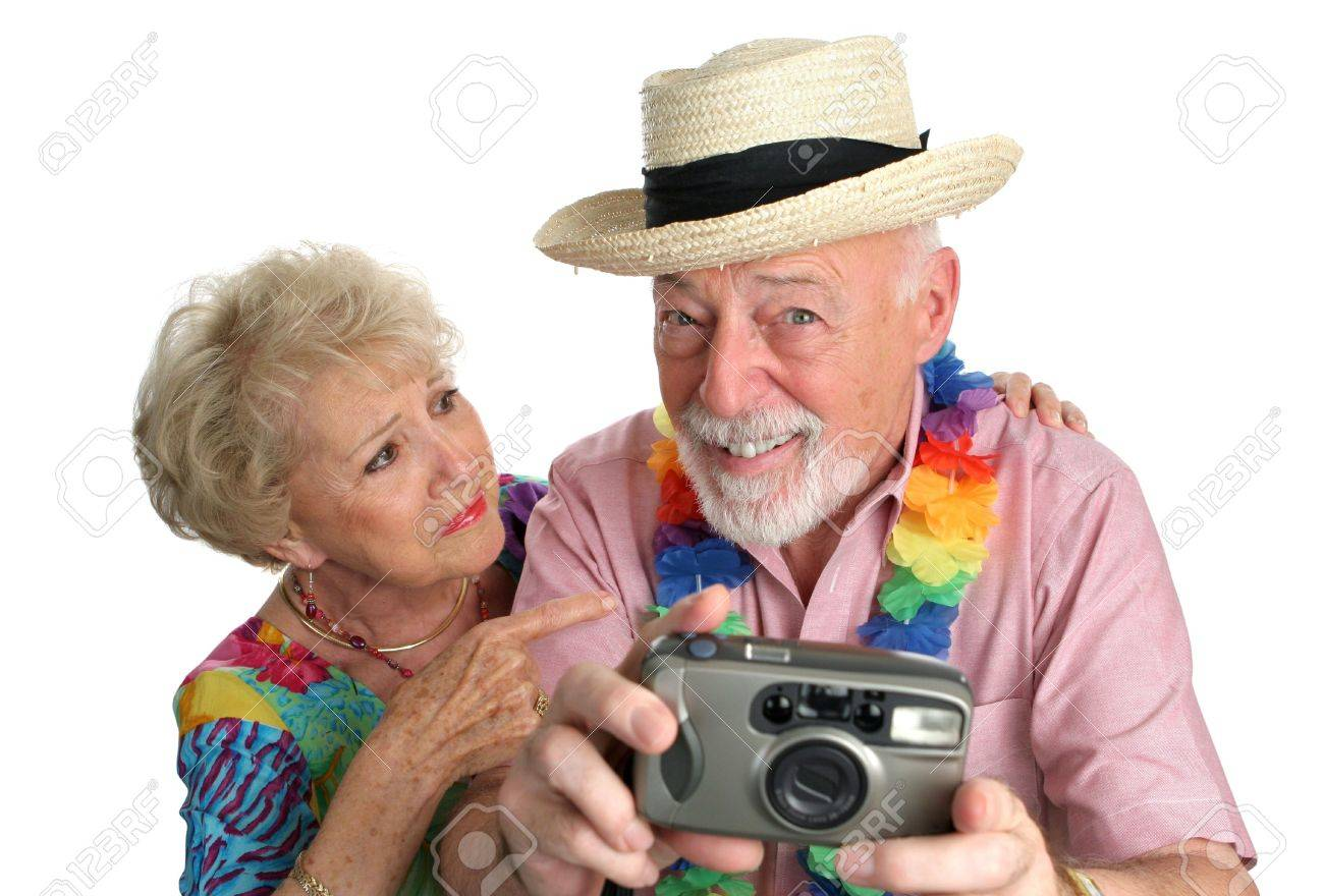 A senior man with a camera taking pictures of pretty girls on the beach while his wife gets mad at him. Stock Photo - 388982