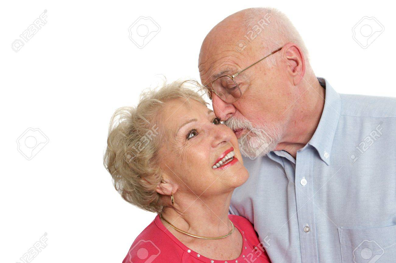 An attractive senior man kissing his beautiful wife on the cheek.  Isolated with room for text. Stock Photo - 414213