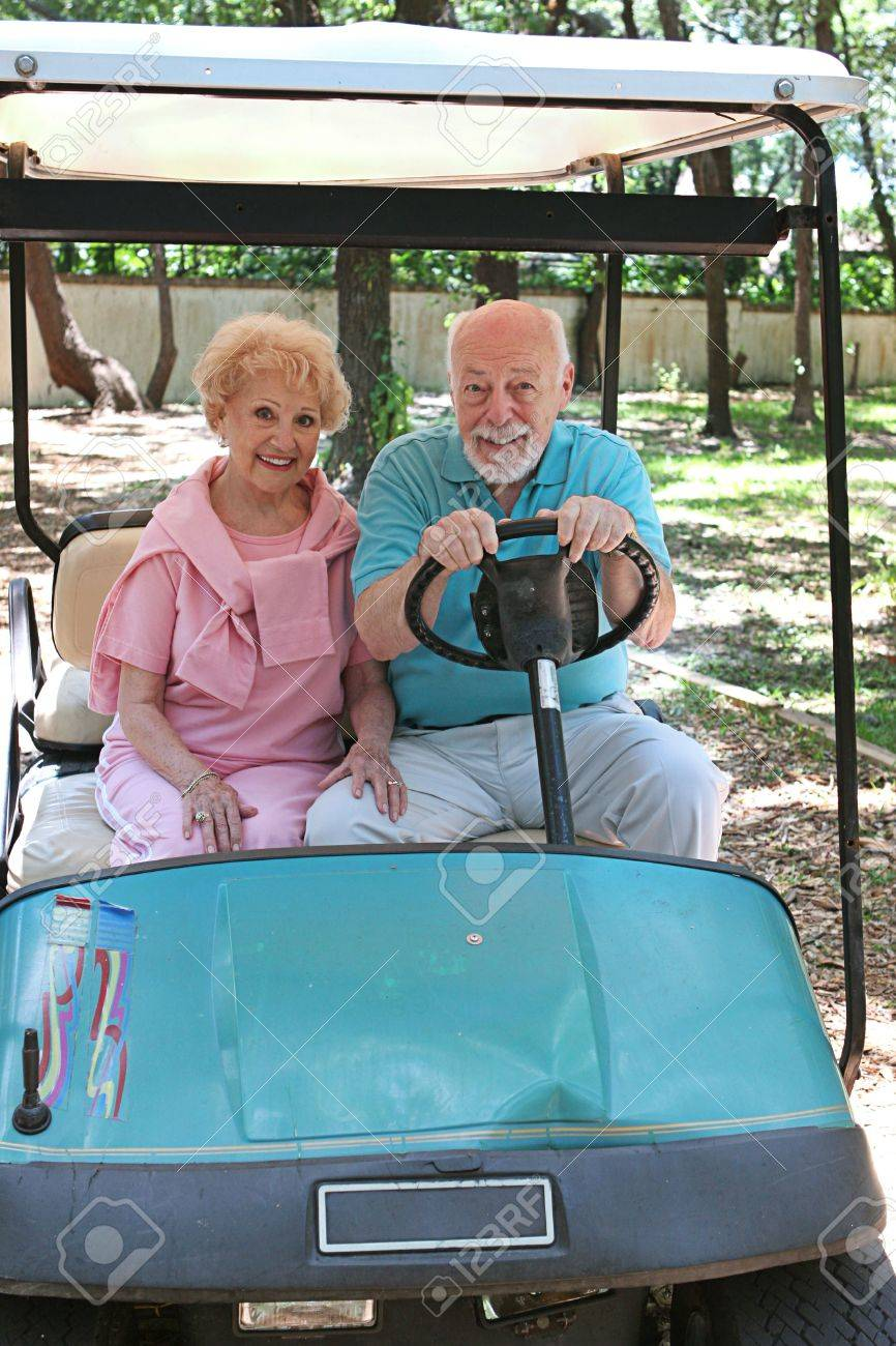A senior couple in a golf cart.  The man wants to drive fast. Stock Photo - 418720