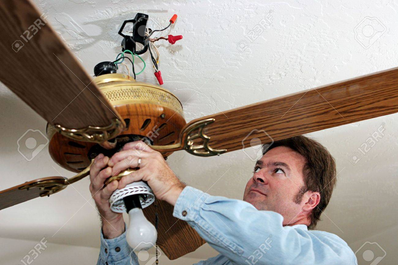 An Electrician Removing Old Ceiling Fan The Was Installed Without A Box