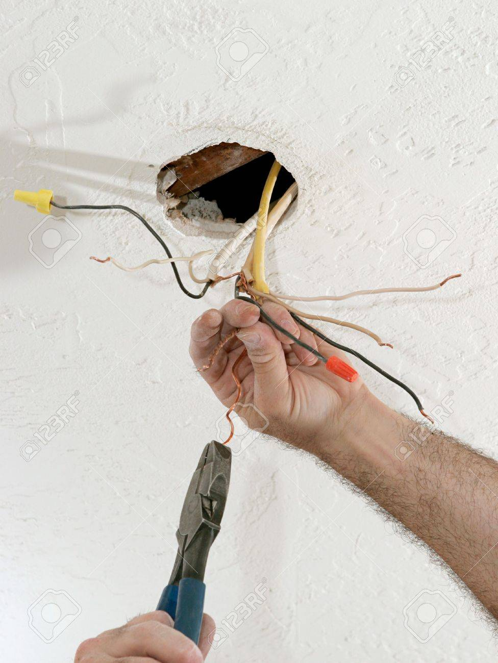 A Closeup Of An Electrician\'s Hands As He Uses Pliers To Straighten ...