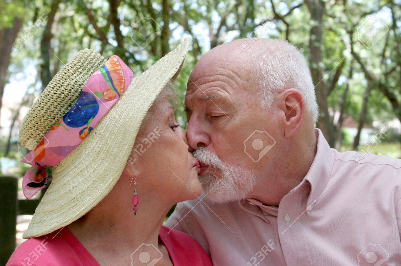 An attractive senior couple kissing outdoors under a canopy of trees. Stock Photo - 460971