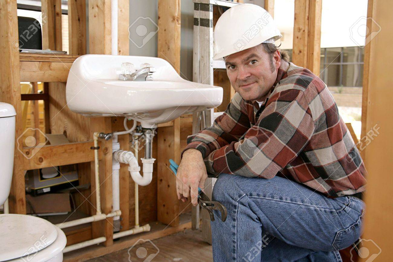 A Construction Plumber Installing Bathroom Fixtures In A Home Under  Construction. Stock Photo   584137