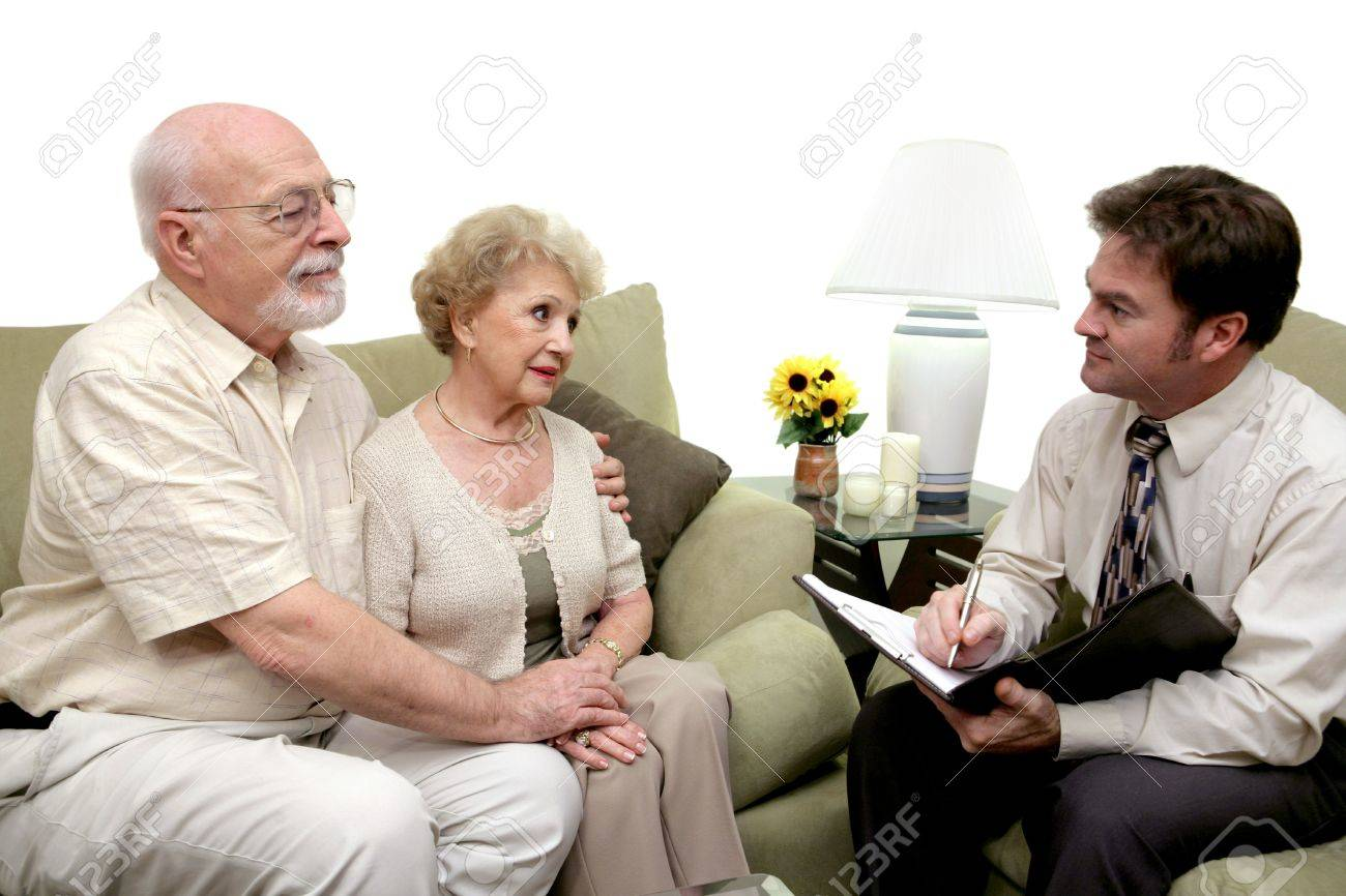 A senior couple speaking with a marriage counselor.  Could also be a salesman in their home.  Isolated on white with focus on couple. Stock Photo - 815505