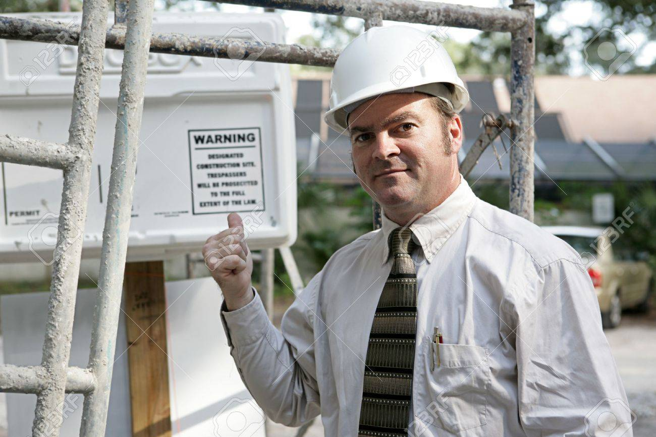 A building inspector standing under scaffolding pointing out the WARNING sign posted on the jobsite. Stock Photo - 877093