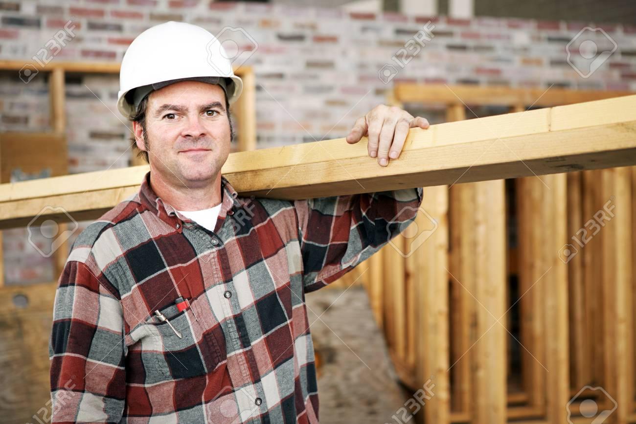 A Construction Day Laborer Carrying Wood Beams. Authentic Construction  Worker On An Actual Construciton Site. Royalty Free Stock-fotók, Képek és  Stock-fotózás. Image 962261.