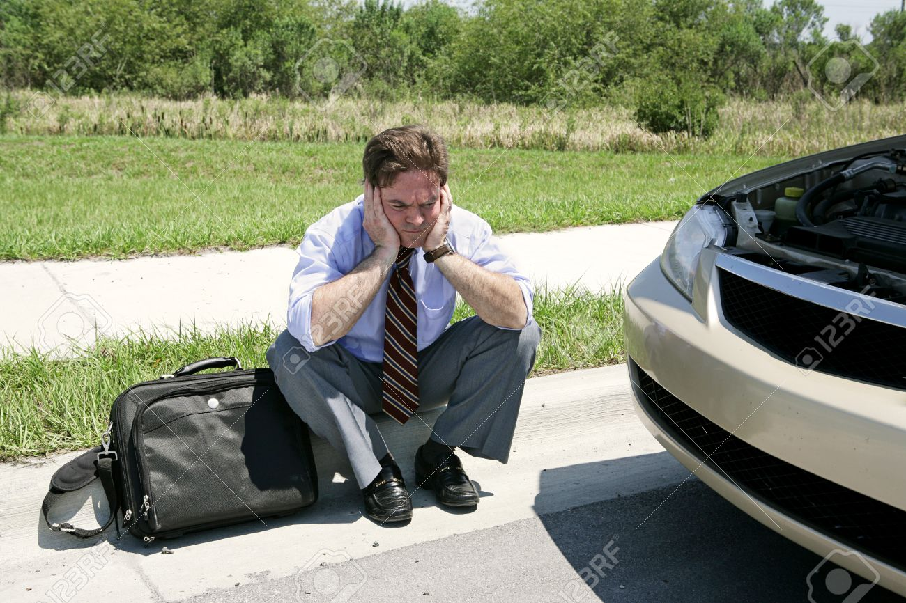 An upset businessman on the side of the road with his broken down car wating for the auto club. Stock Photo - 1518608