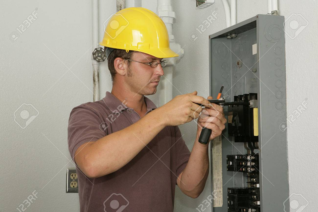 An electrician working on an industrial breaker panel.  Model is an actual electrician performing all work to industry codes and safety standards. Stock Photo - 1573346