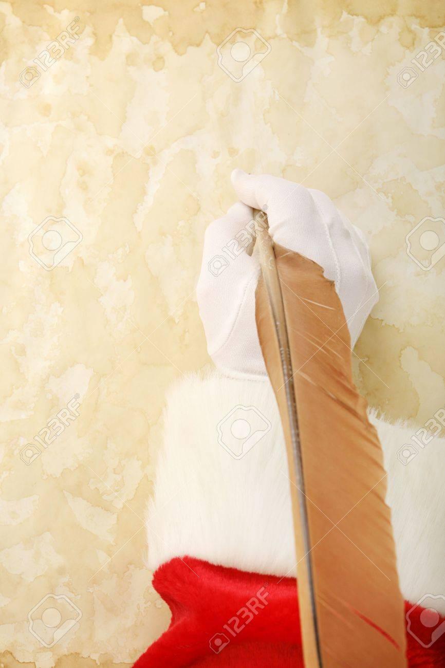 Santas mano usando una pluma pluma para escribir en papel pergamino de edad.  Foto de archivo - 1962515