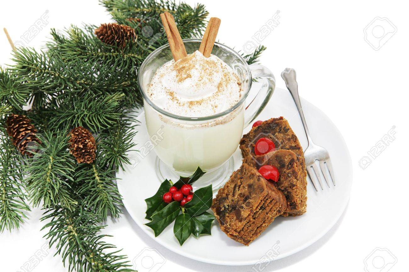 Holiday fruitcake and eggnog on a plate garnished with holly and surrounded by pine branches.  White background. Stock Photo - 2018650