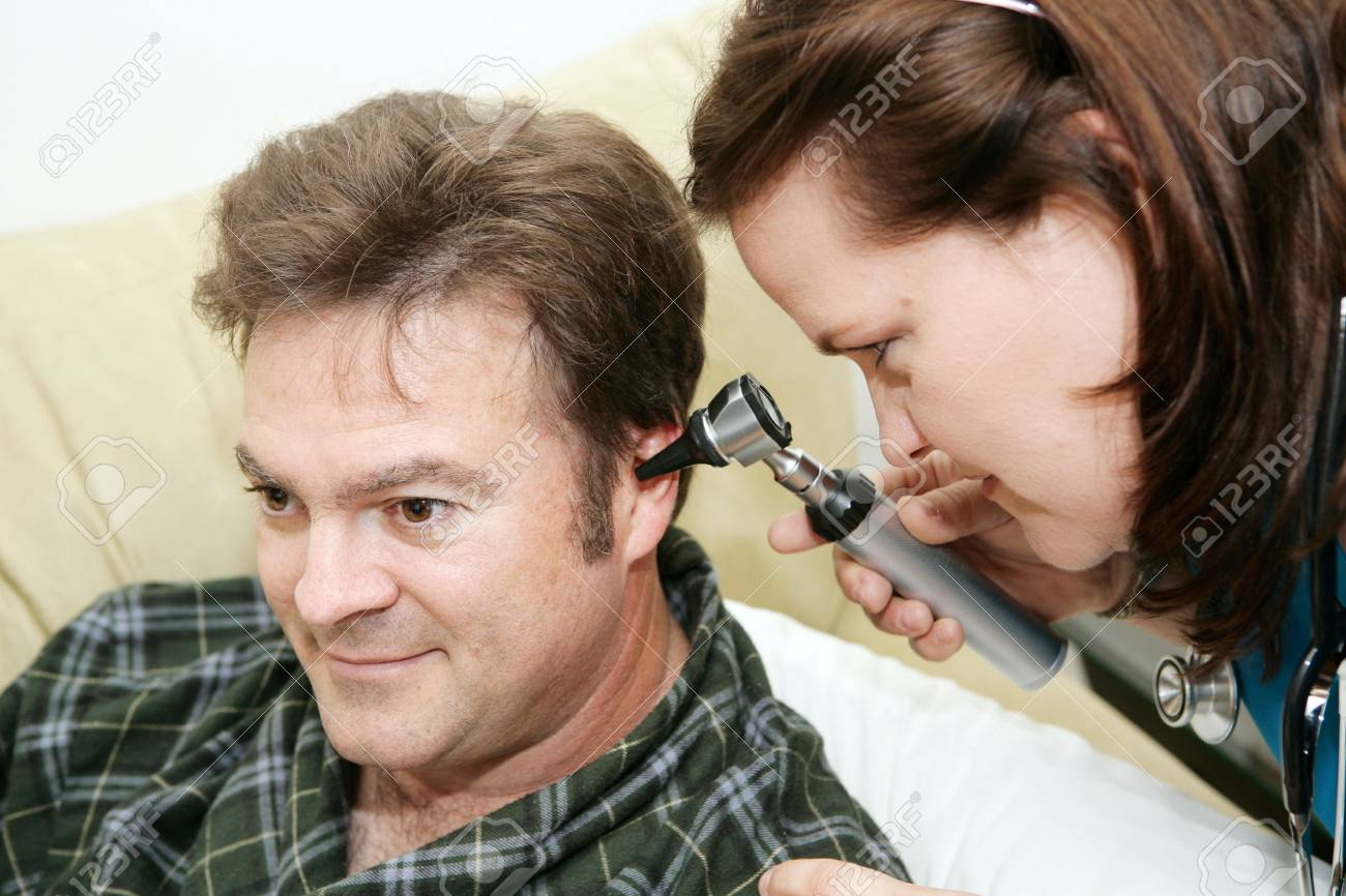 Home health nurse using an otoscope to look in her patient's ears. Stock Photo - 2192693